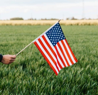 crop faceless person showing american flag on field in daytime